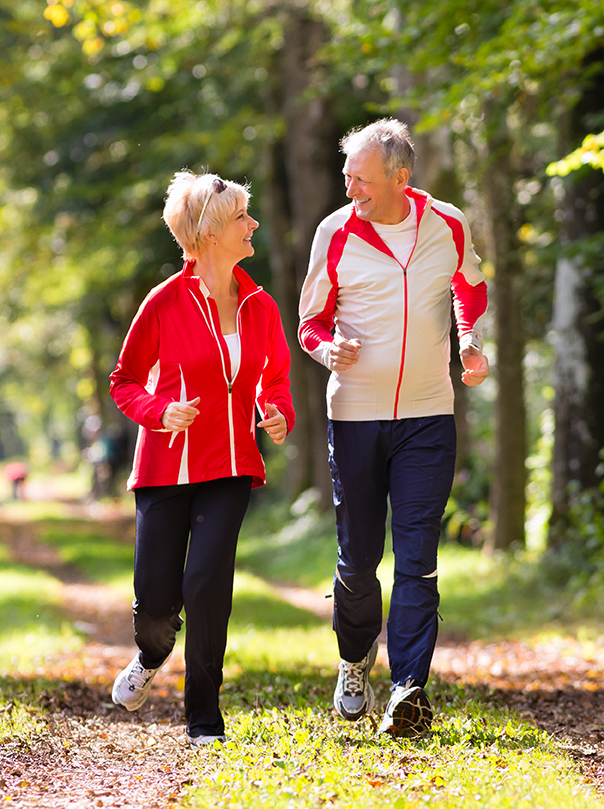 Senior couple jogging on a forest path.