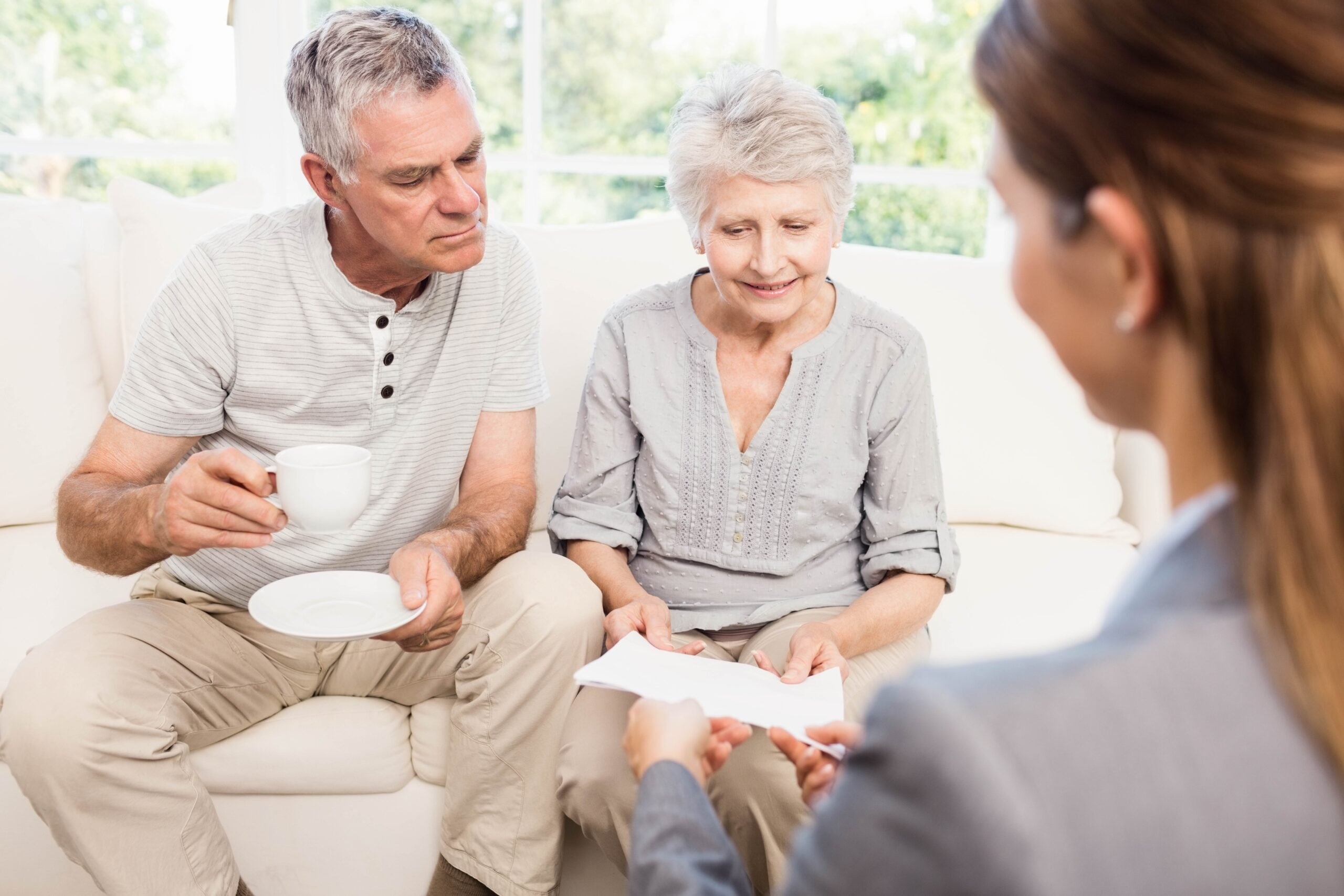 Seniors examine documents with professional specialist in their living room over tea