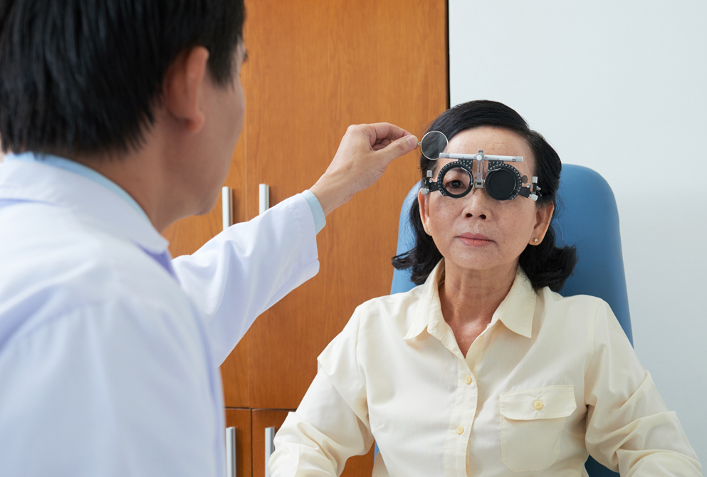 Senior Asian woman has eyes examined by younger doctor