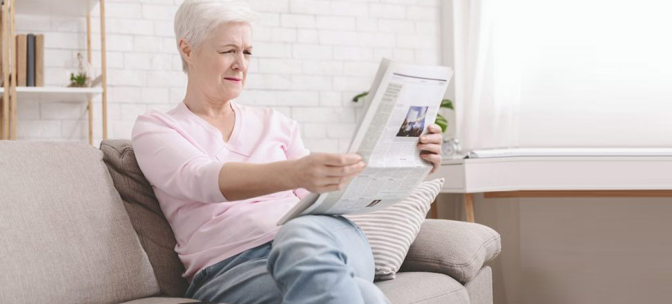 Senior woman struggles to read newspaper in living room