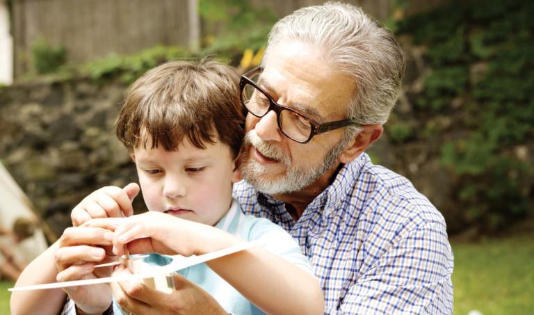 Senior man helps grandson with model plane