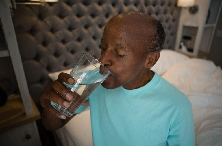 Older man having a glass of water before going to bed