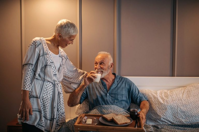 Older man being given a light meal before bed by his wife