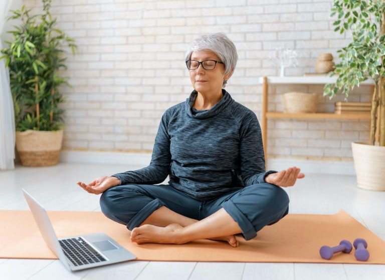 Senior woman practicing yoga online at home using laptop
