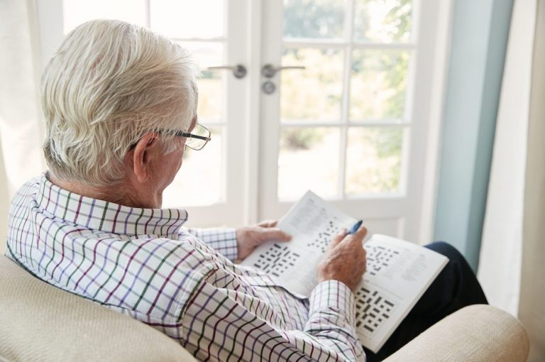Senior man does crossword puzzle at home