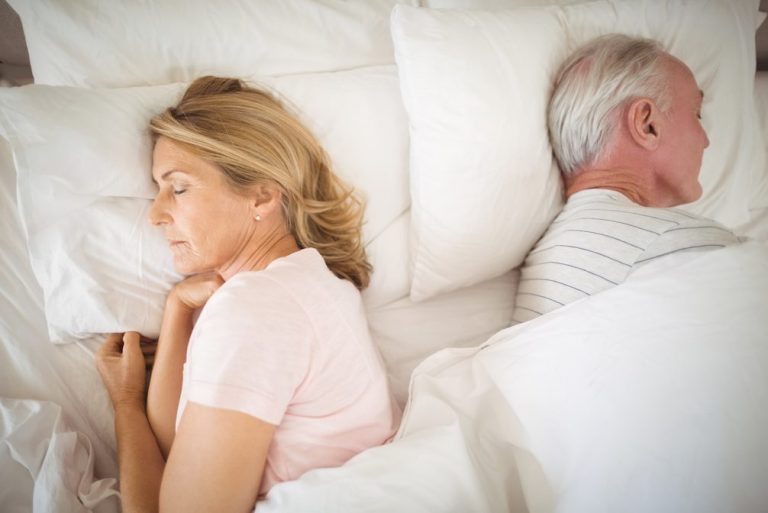 Senior couple asleep in bed apart