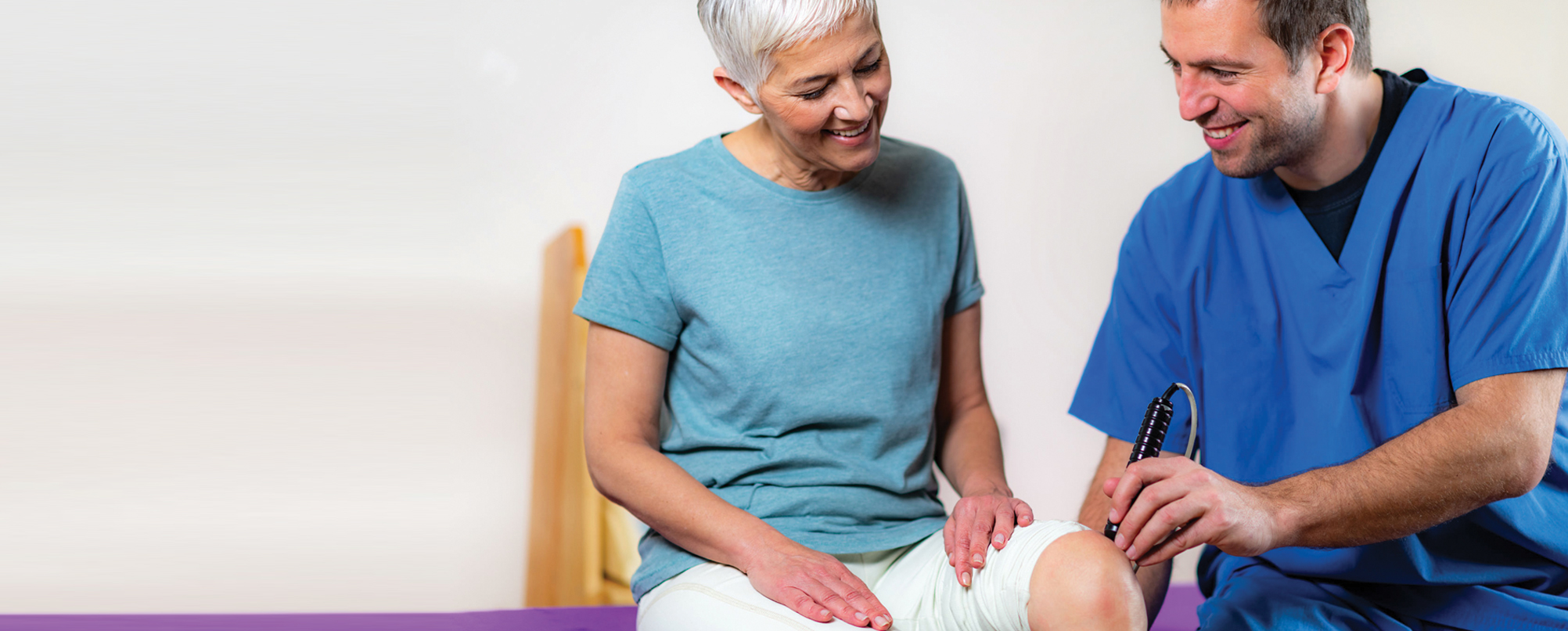 Happy senior woman has knee examined by young professional specialist