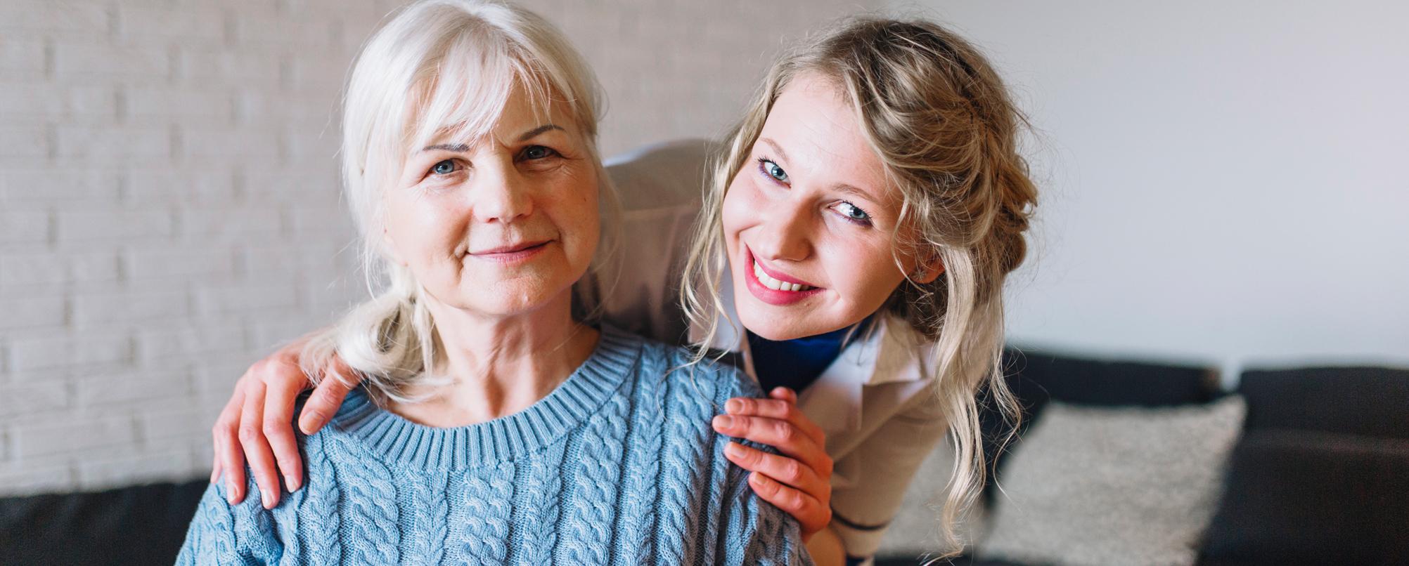 Senior woman and carer posing for camera