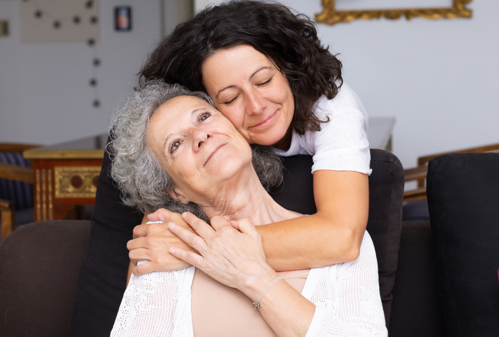 Senior woman hugged by daughter from behind