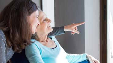 Senior woman sits by sunny window with daughter