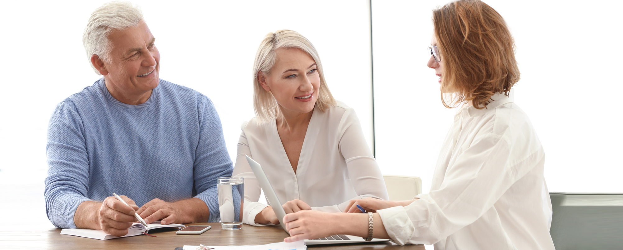 Senior couple consults with younger professional specialist using a laptop