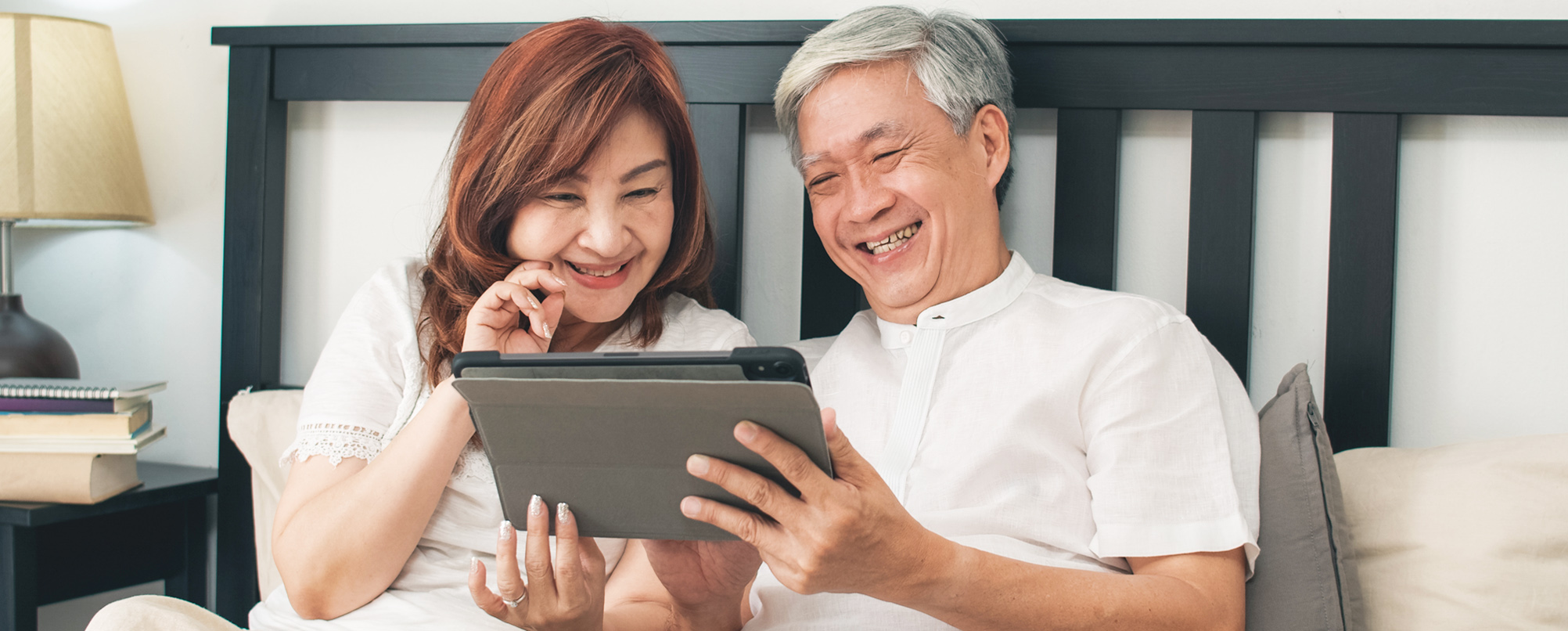 Happy Asian senior couple using tablet in bed
