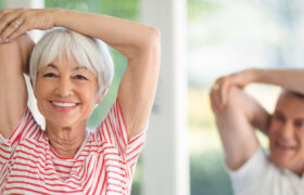 Senior woman stretching and exercising with another in the background