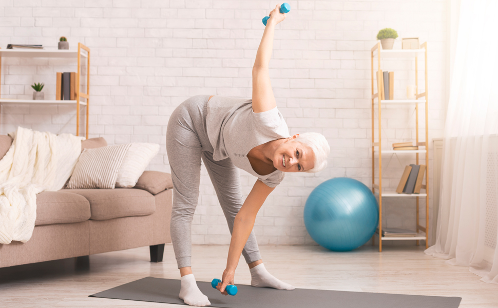 Senior woman exercising and stretching with small weights in living room