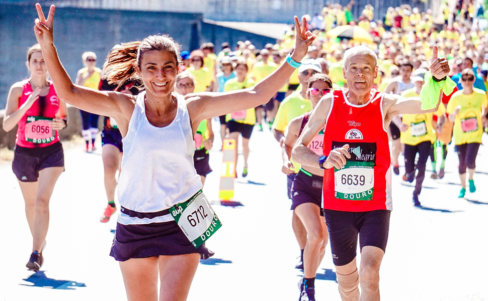 Young woman and senior man lead group running a marathon