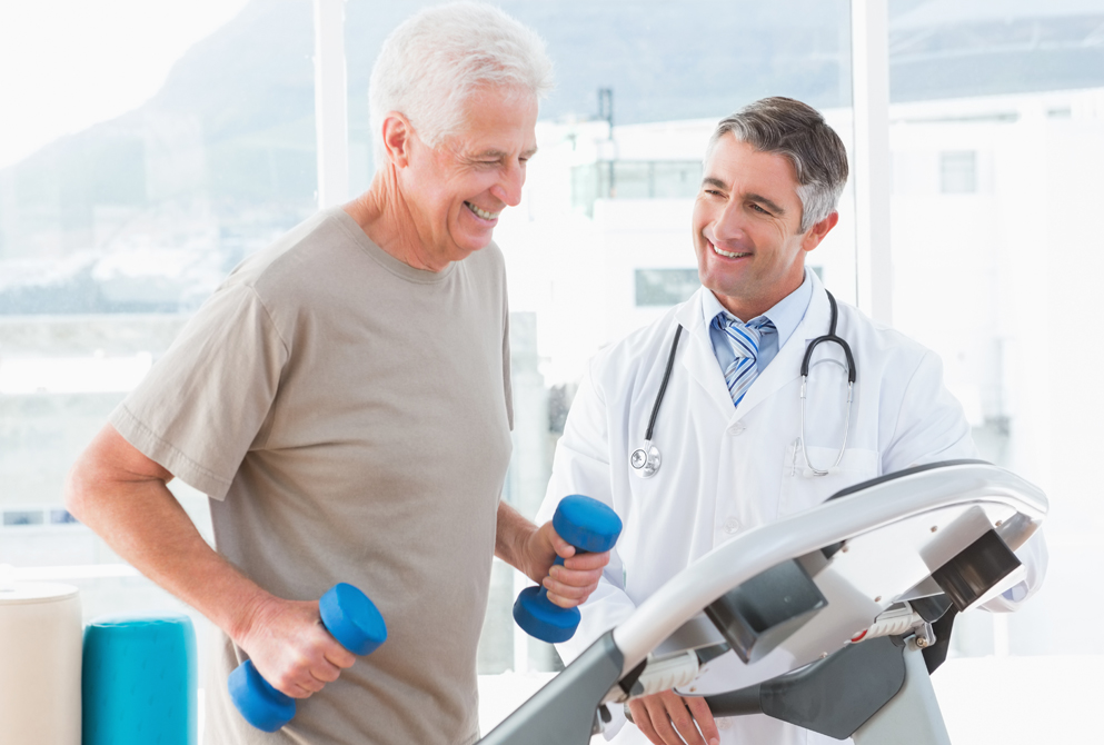 Man on treadmill with small weights and smiling doctor.