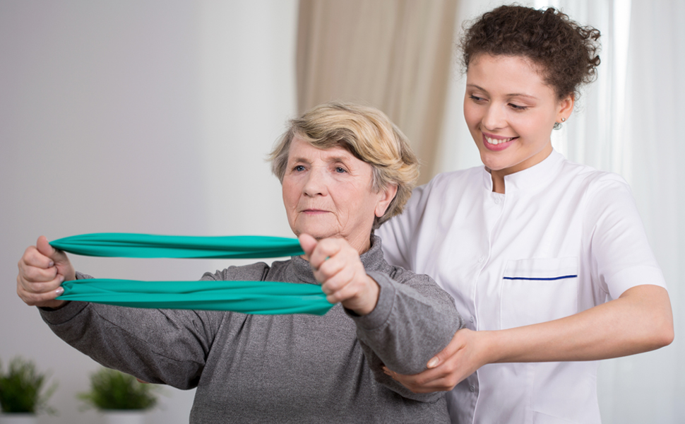 Senior woman practices stretching exercise assisted by younger health specialist professional