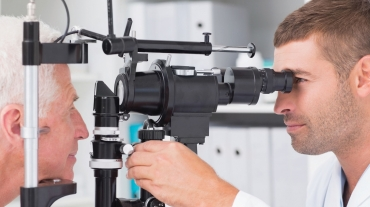 Senior man has eyes tested by younger professional specialist