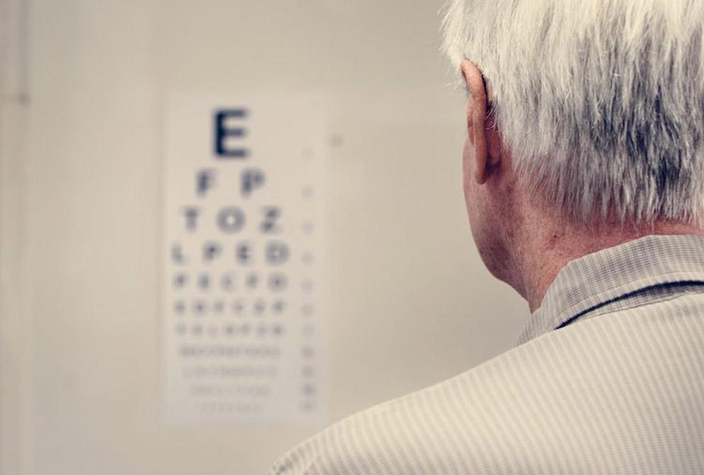 Senior man takes eye test with eye chart