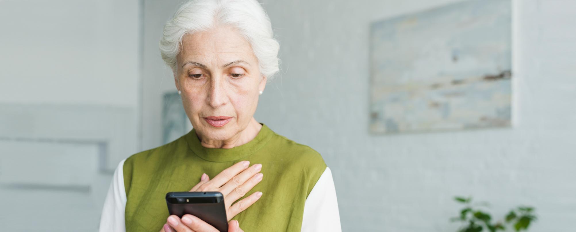 Senior woman surprised by news on phone