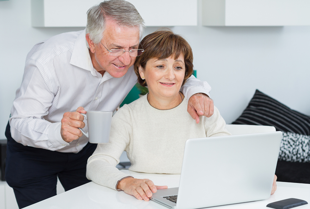 Happy senior couple browsing internet on laptop in living room