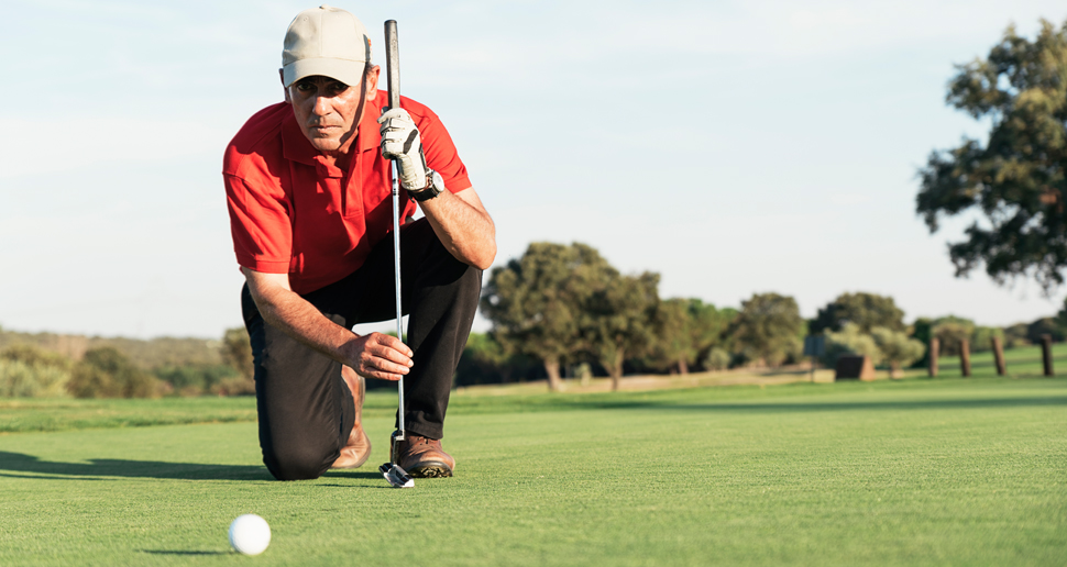 Senior man playing golf examines golf ball on green golf course