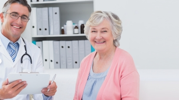 Happy senior woman poses in doctor's office