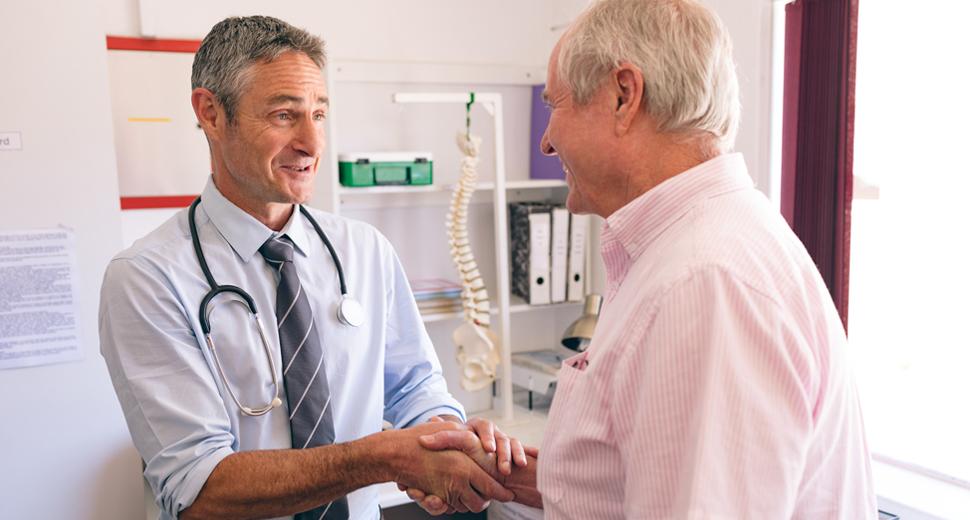 Happy senior man shakes doctor's hand