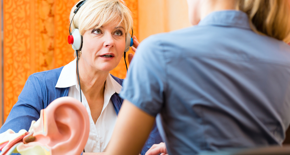 Senior woman takes hearing test administered by professional specialist