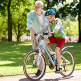 Senior man teaches grandson to ride bike in park