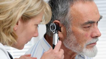 Doctor checks ears of senior man as part of hearing test