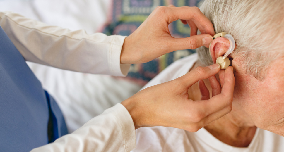 Senior hearing aid administered by doctor