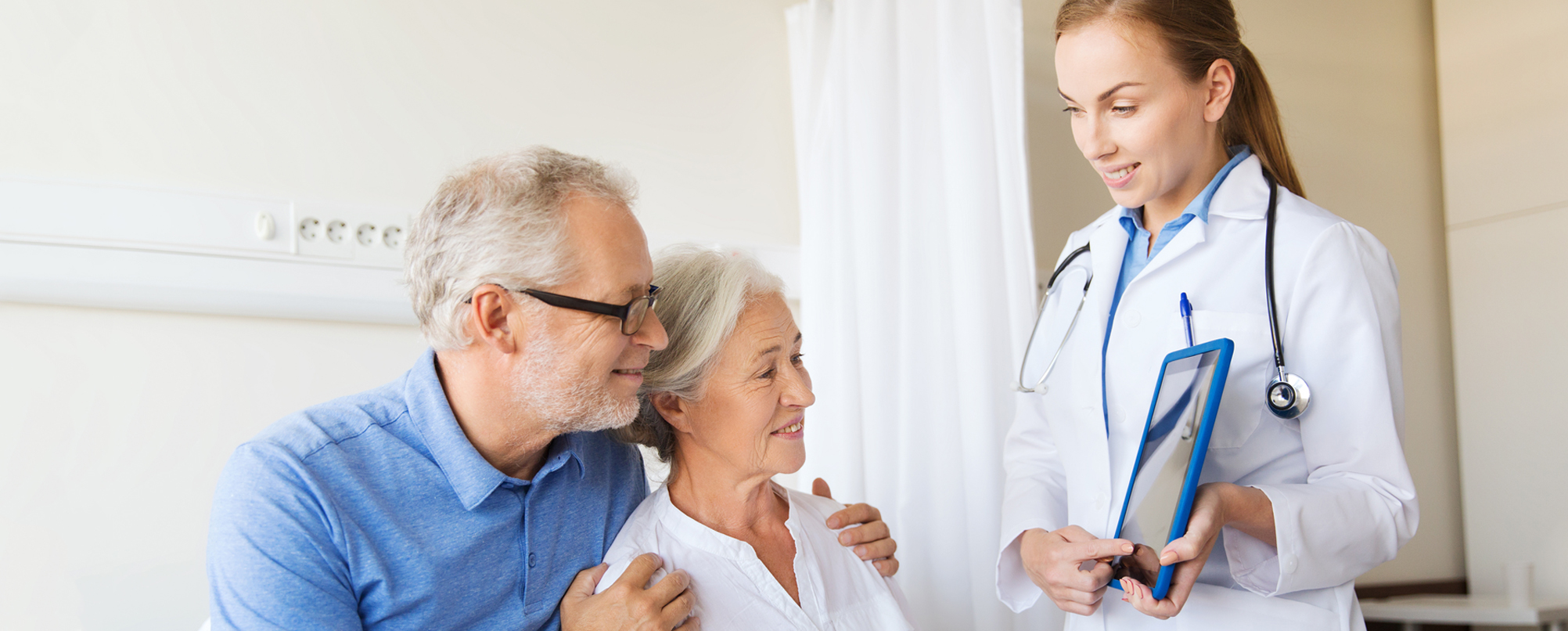 Doctor presents senior couple with information using tablet