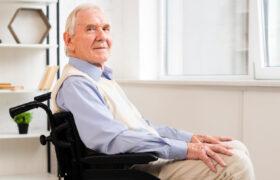 Senior man in wheelchair poses for photo