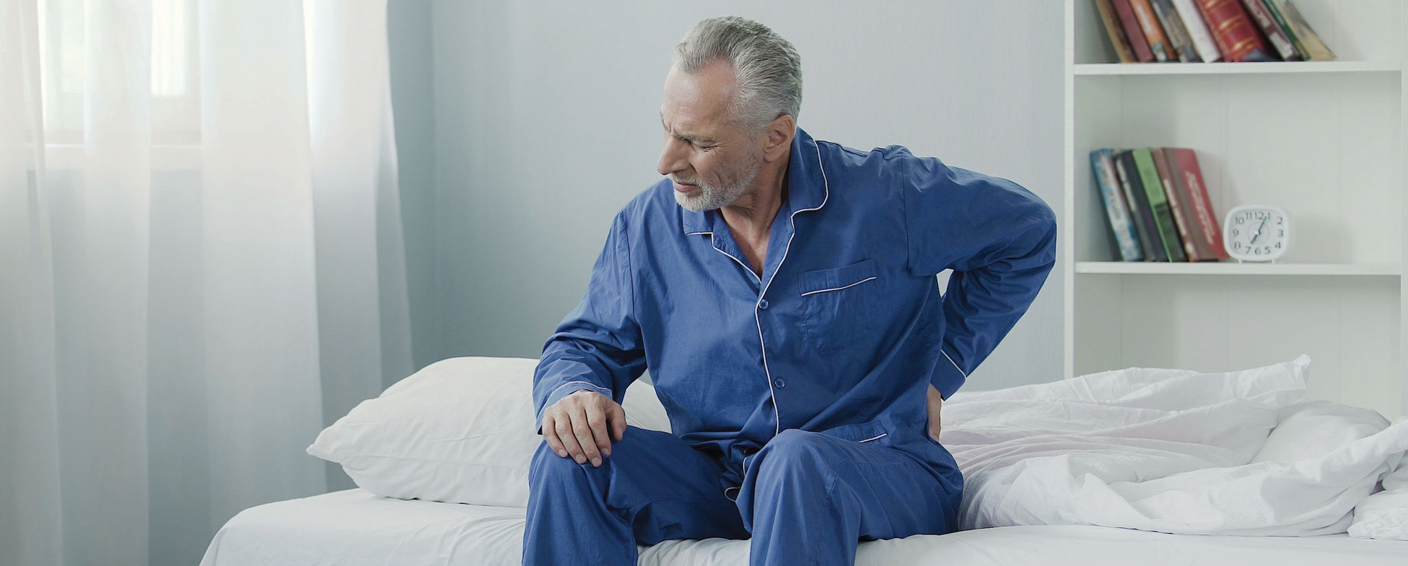 Senior man in bed wakes up with back pain