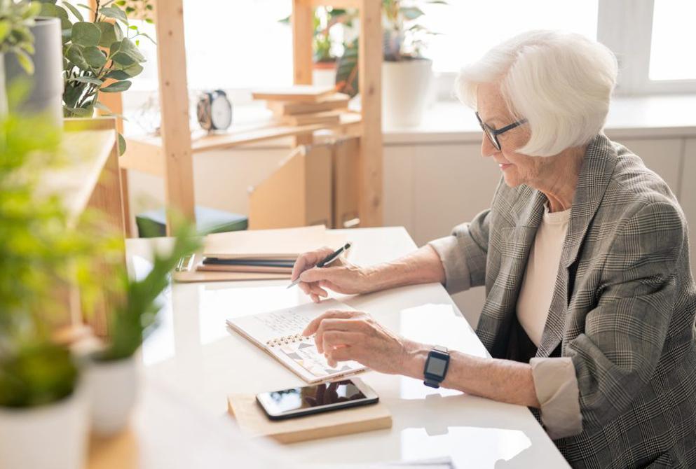 Senior woman writes in journal or diary.