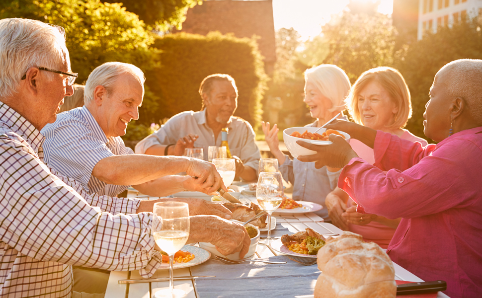 Group of seniors enjoying picnic dinner in garden at sunset