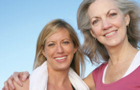 Two happy senior women smile and pose for photo
