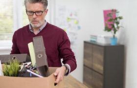 Uncertain senior man cleans out desk leaving a job