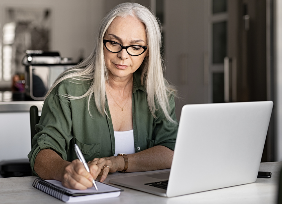 Serious senior woman making notes and using laptop in kitchen