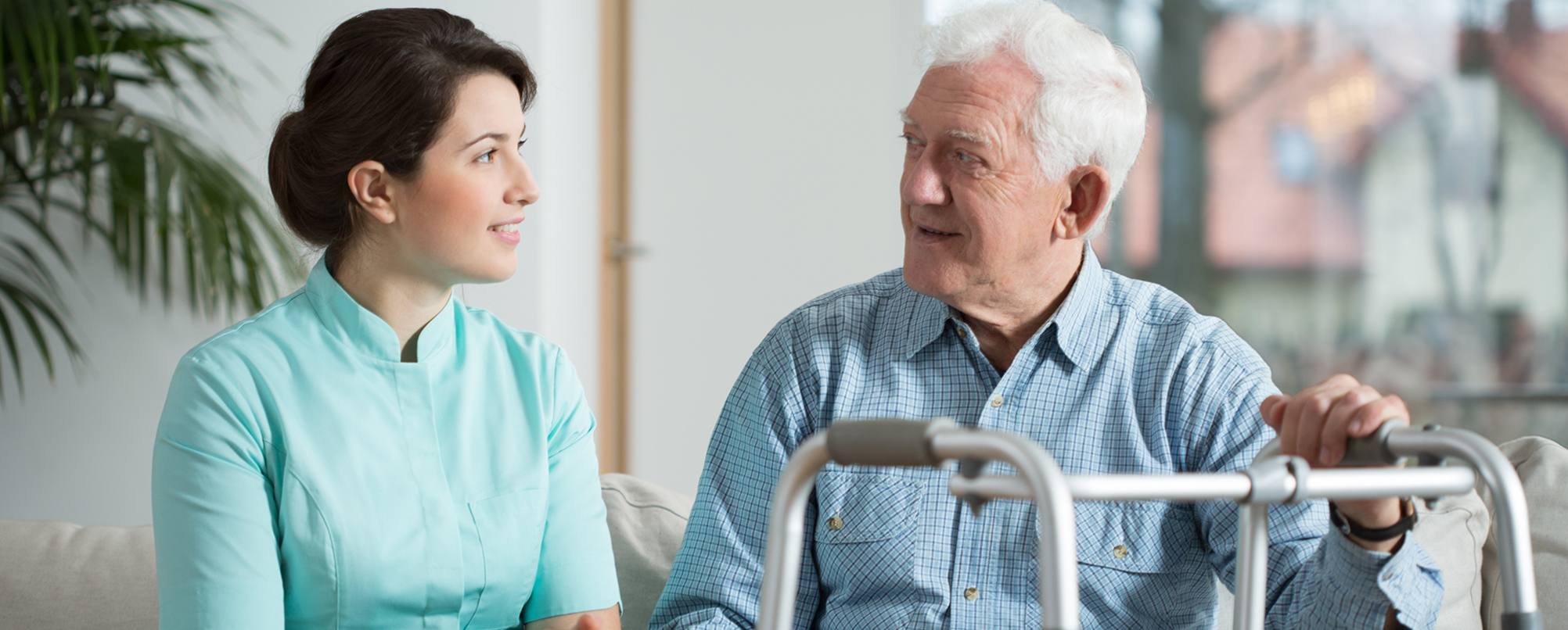 Senior man with walker speaks with younger professional health specialist