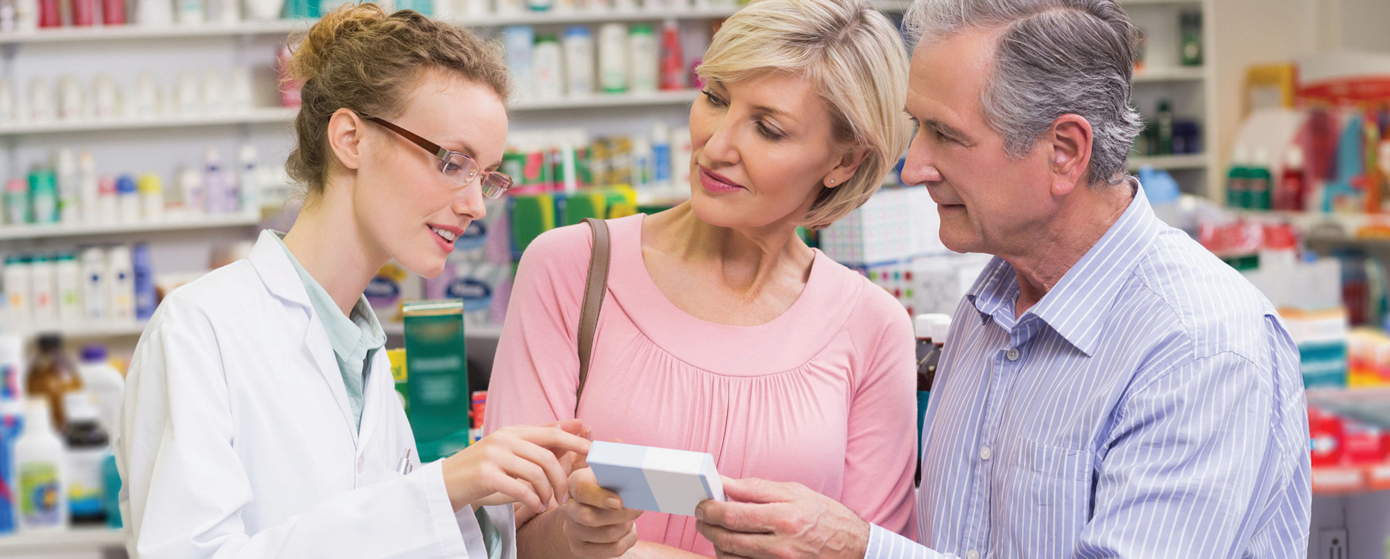 Senior couple speaks to pharmacist about medication package in pharmacy