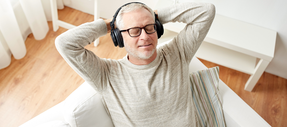Senior man relaxing at home listening to music