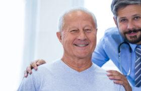 Senior man smiling for photo while carer holds shoulders