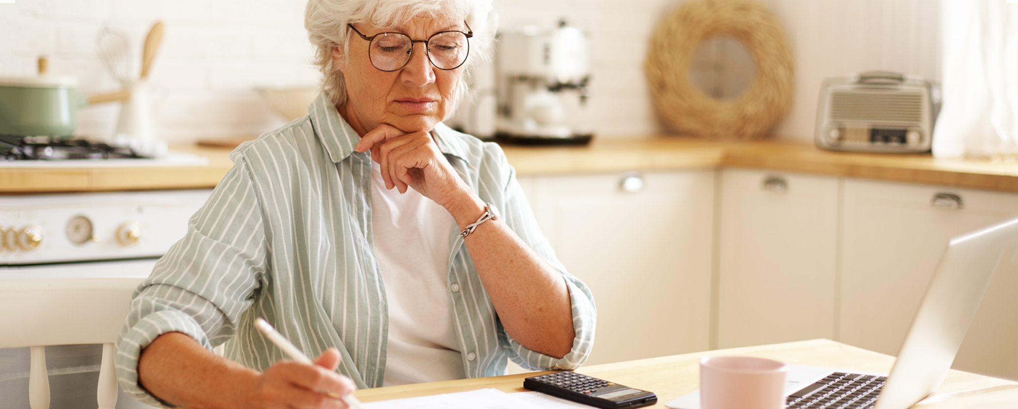 Stressed senior woman calculates finances in kitchen with laptop