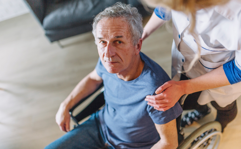 Senior man in wheelchair supported by carer