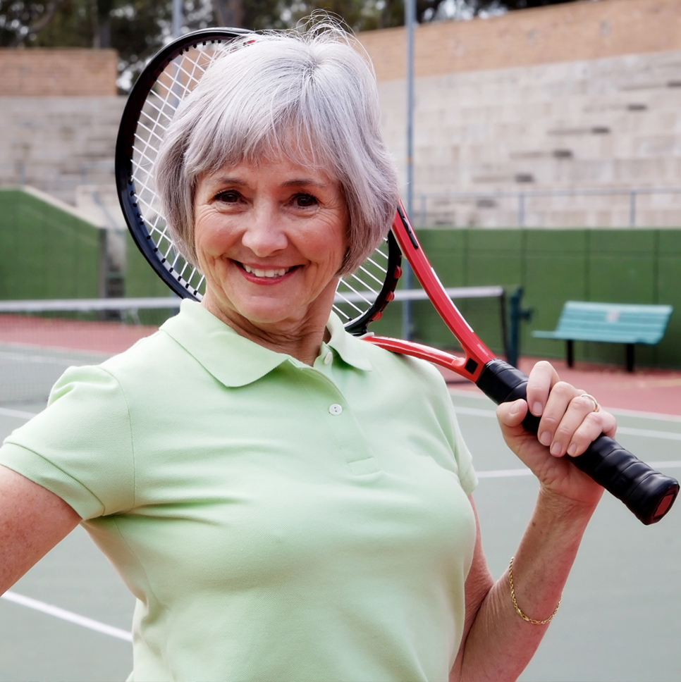 Senior woman poses with racquet on tennis court