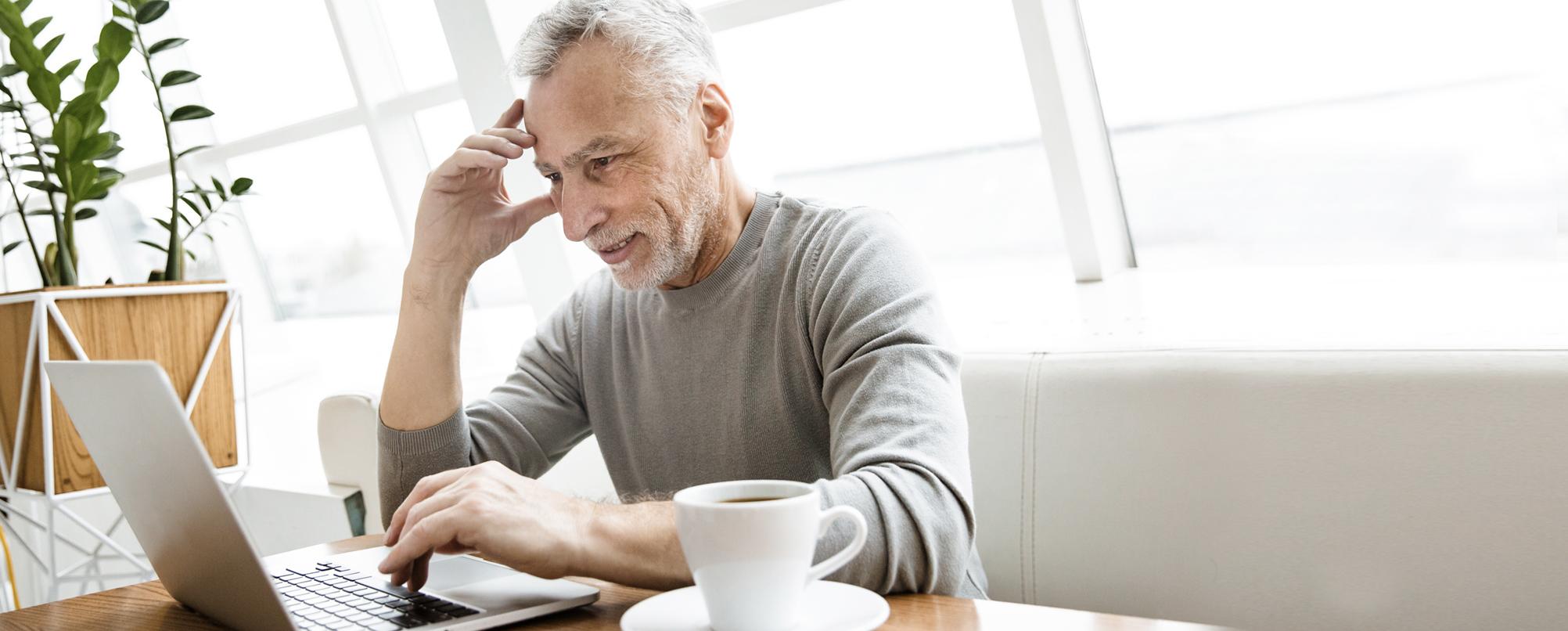 Stressed senior man browses on laptop in café
