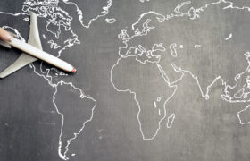 Stock image of toy plane on drawing of world map