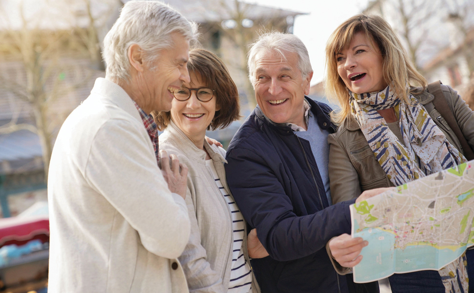 Happy group of tow senior couples reading a map in a new city